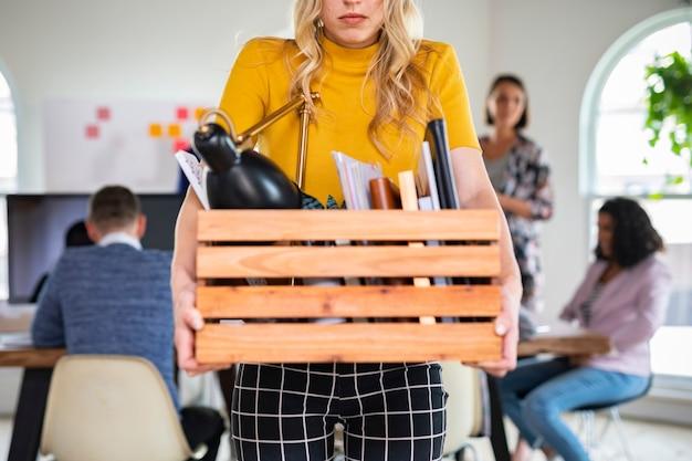 Jonge zakenvrouw die een houten kist draagt