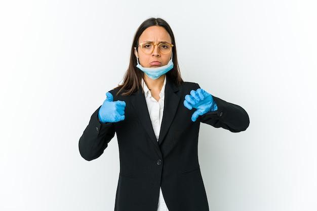 Jonge zakenvrouw die een masker draagt om te beschermen tegen covid geïsoleerd op een witte muur met duimen omhoog en duimen omlaag, moeilijk kies concept