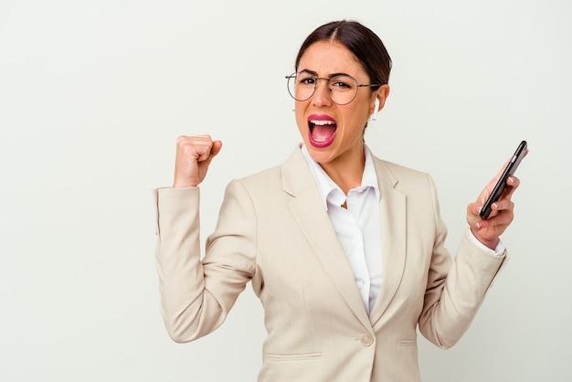 Jonge zakenvrouw die een mobiele telefoon houdt die op witte achtergrond wordt geïsoleerd en vuist opheft na een overwinning, winnaarconcept.