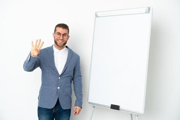 Jonge zakenvrouw die een presentatie geeft op een wit bord geïsoleerd op een witte achtergrond gelukkig en vier tellen met vingers