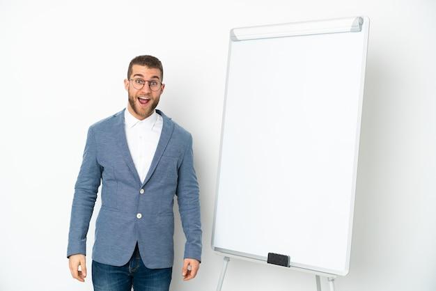 Jonge zakenvrouw die een presentatie geeft op wit bord geïsoleerd op wit met verrassingsgelaatsuitdrukking