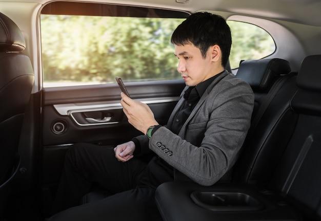 Jonge zakenvrouw die een smartphone gebruikt terwijl ze op de achterbank van de auto zit