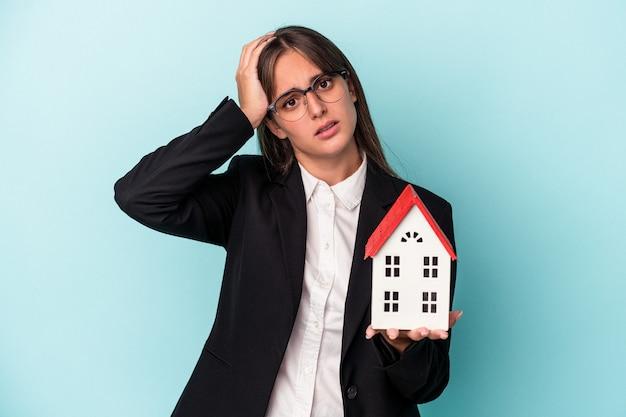 Jonge zakenvrouw die een speelgoedhuis vasthoudt dat op een blauwe achtergrond wordt geïsoleerd en geschokt is, herinnert zich een belangrijke vergadering.