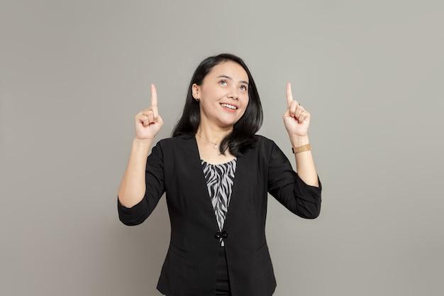 Jonge zakenvrouw die een zwart pak draagt en omhoog kijkt met twee handen