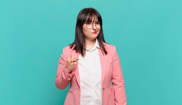 Jonge zakenvrouw die er arrogant, succesvol, positief en trots uitziet, wijzend naar zichzelf