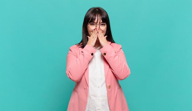 Jonge zakenvrouw die er blij, vrolijk, gelukkig en verrast uitziet en de mond bedekt met beide handen