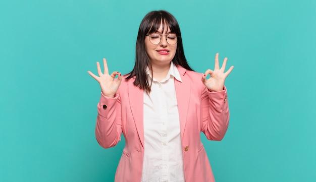 Jonge zakenvrouw die er geconcentreerd uitziet en mediteert, zich tevreden en ontspannen voelt, nadenkt of een keuze maakt