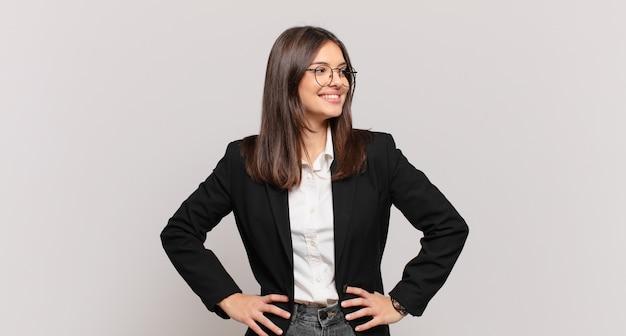 Jonge zakenvrouw die er gelukkig, vrolijk en zelfverzekerd uitziet, trots lacht en opzij kijkt met beide handen op de heupen