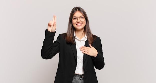 Jonge zakenvrouw die er gelukkig, zelfverzekerd en betrouwbaar uitziet, glimlacht en een overwinningsteken toont, met een positieve houding