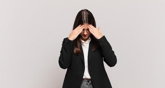 Jonge zakenvrouw die er gestrest en gefrustreerd uitziet, onder druk werkt met hoofdpijn en last heeft van problemen
