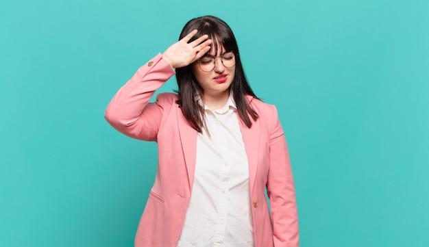 Jonge zakenvrouw die er gestrest, moe en gefrustreerd uitziet, het zweet van het voorhoofd droogt, zich hopeloos en uitgeput voelt