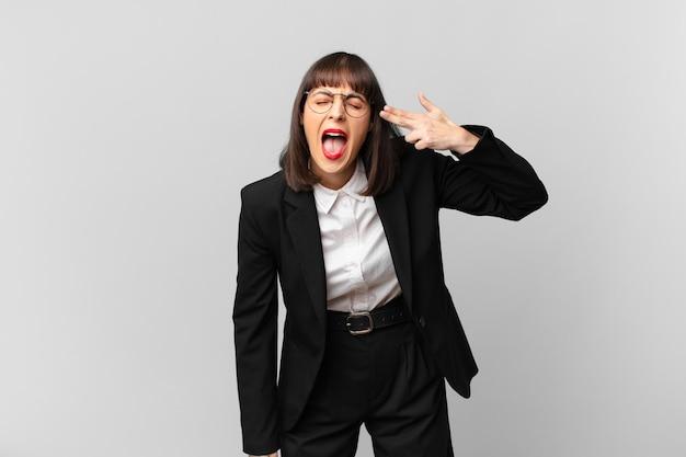 Jonge zakenvrouw die er ongelukkig en gestrest uitziet, zelfmoordgebaar maakt een pistoolteken met de hand, wijzend naar het hoofd