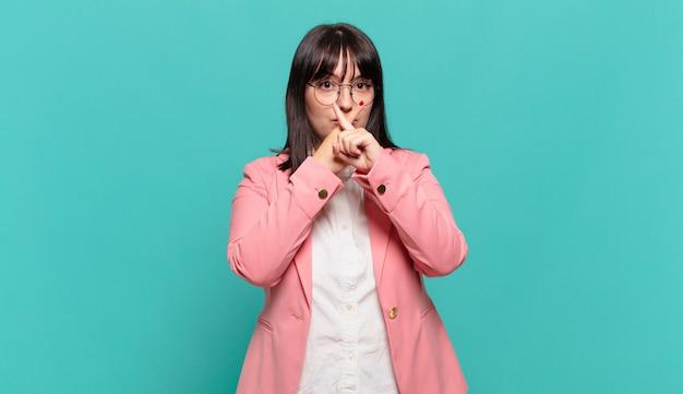 Jonge zakenvrouw die er serieus en ontevreden uitziet met beide vingers vooraan gekruist in afwijzing, en vraagt om stilte