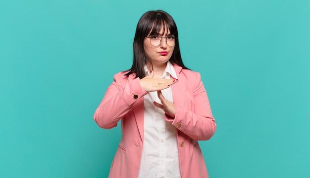 Jonge zakenvrouw die er serieus, streng, boos en ontevreden uitziet, waardoor een time-out teken wordt