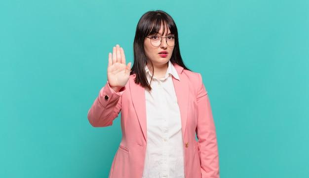 Jonge zakenvrouw die er serieus, streng, ontevreden en boos uitziet en een open palm laat zien die een stopgebaar maakt