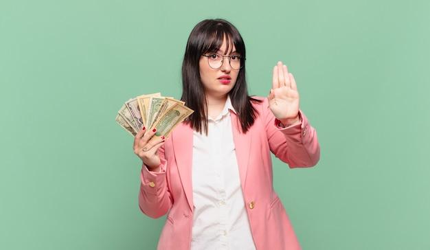 Jonge zakenvrouw die er serieus, streng, ontevreden en boos uitziet met een open palm die een stopgebaar maakt