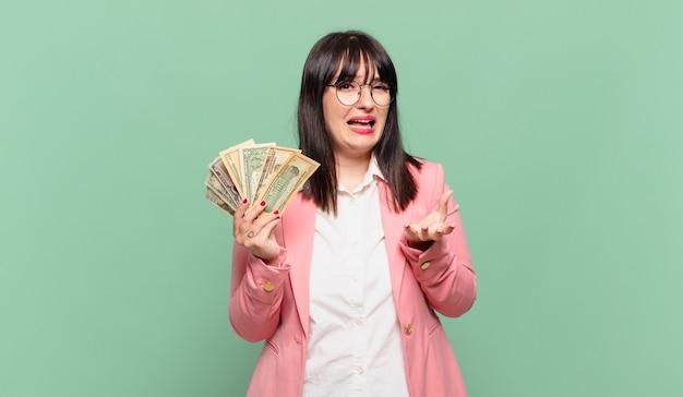 Jonge zakenvrouw die er wanhopig en gefrustreerd, gestrest, ongelukkig en geïrriteerd uitziet, schreeuwend en schreeuwend