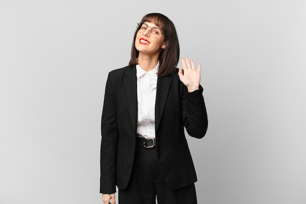 Jonge zakenvrouw die gelukkig en opgewekt glimlacht, met de hand zwaait, u verwelkomt en begroet, of afscheid neemt