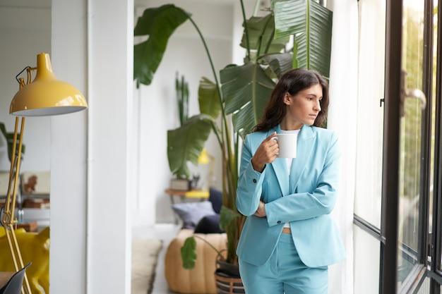 Jonge zakenvrouw die geniet van ontspannen met haar koffie of thee in de ochtend en uit het raam kijkt prachtig...