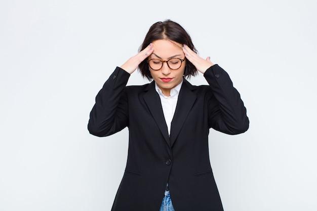 Jonge zakenvrouw die gestrest en gefrustreerd kijkt, onder druk werkt met hoofdpijn en problemen heeft tegen een witte muur