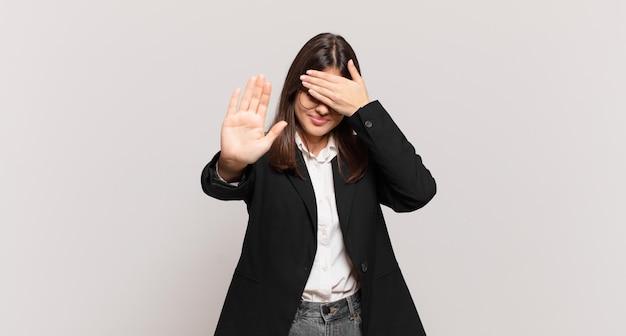 Jonge zakenvrouw die het gezicht met de hand bedekt en de andere hand naar voren steekt om de camera te stoppen, foto's of afbeeldingen te weigeren
