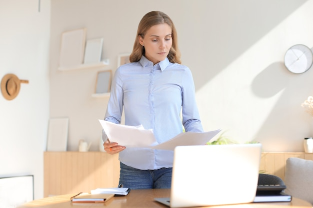 Jonge zakenvrouw die in haar kantoor aan huis notities leest.