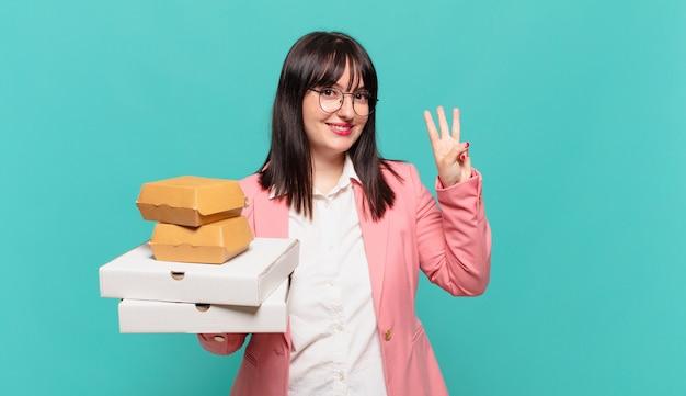 Jonge zakenvrouw die lacht en er vriendelijk uitziet, nummer drie of derde toont met de hand naar voren, aftellend