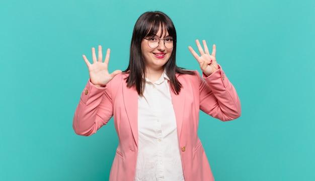 Jonge zakenvrouw die lacht en er vriendelijk uitziet, nummer negen of negende toont met de hand naar voren, aftellend