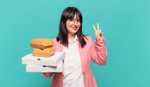 Jonge zakenvrouw die lacht en er vriendelijk uitziet, nummer twee of seconde toont met de hand naar voren, aftellend