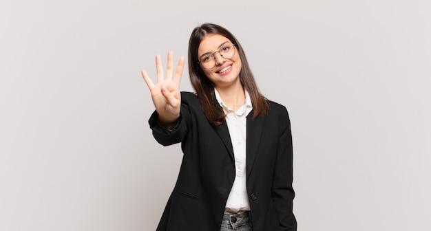 Jonge zakenvrouw die lacht en er vriendelijk uitziet, nummer vier of vierde toont met de hand naar voren, aftellend