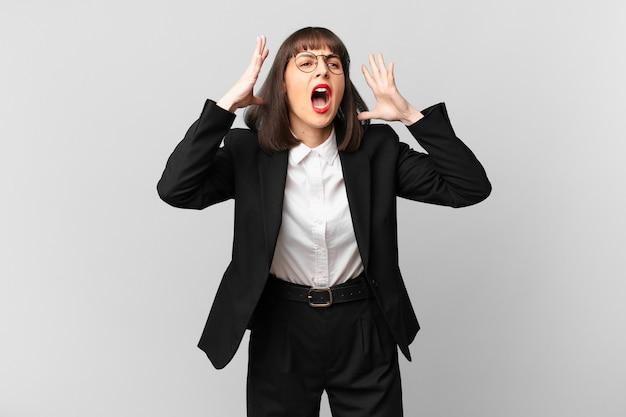 Jonge zakenvrouw die met de handen in de lucht schreeuwt, zich woedend, gefrustreerd, gestrest en overstuur voelt