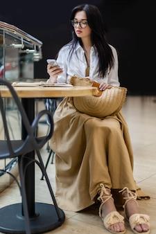 Jonge zakenvrouw die op afstand werkt in een openbare cafetaria die aan het chatten is met een smartphone die aan tafel zit