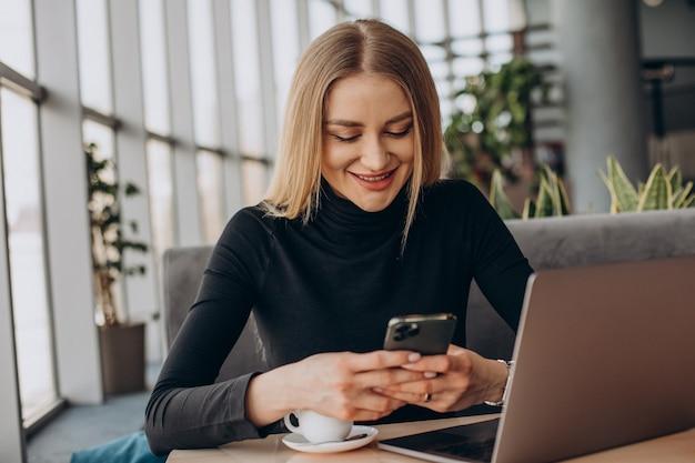 Jonge zakenvrouw die op laptop in een café werkt