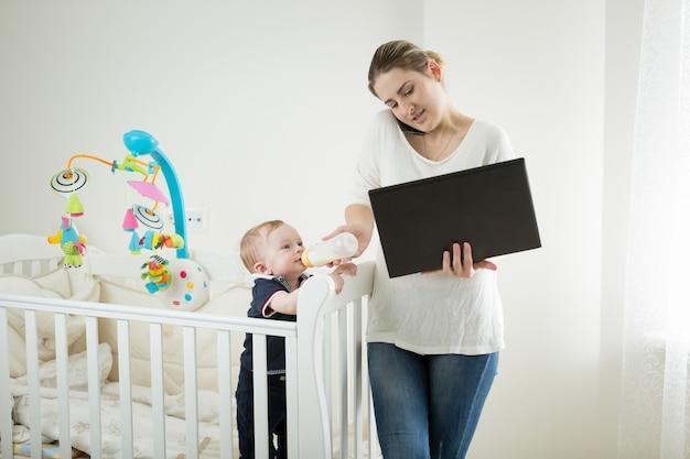 Jonge zakenvrouw die thuis werkt met haar 9 maanden oude baby