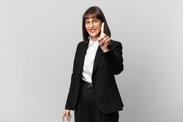 Jonge zakenvrouw die trots en zelfverzekerd glimlacht en nummer één triomfantelijk poseert, voelt zich een leider