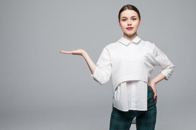 Jonge zakenvrouw die u verwelkomt geïsoleerd op een witte muur