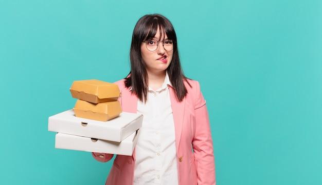 Jonge zakenvrouw die verbaasd en verward kijkt, lip bijt met een nerveus gebaar, niet wetend het antwoord op het probleem