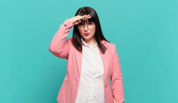 Jonge zakenvrouw die verbijsterd en verbaasd kijkt, met hand over voorhoofd ver weg kijkend, kijkend of zoekend