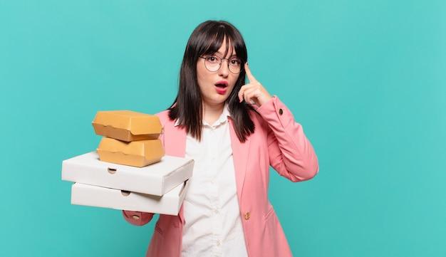 Jonge zakenvrouw die verrast, met open mond, geschokt kijkt en een nieuwe gedachte, idee of concept realiseert