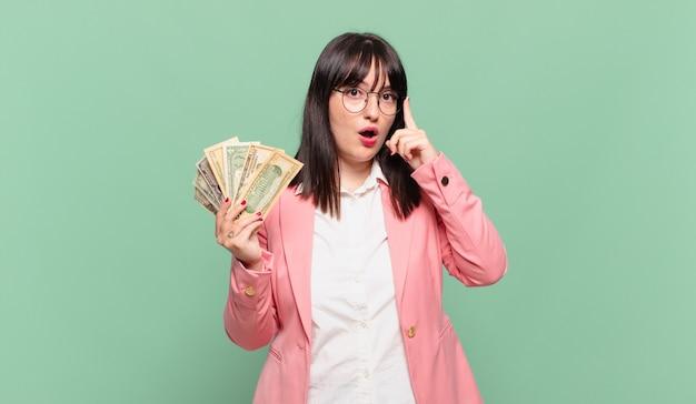 Jonge zakenvrouw die verrast, met open mond, geschokt kijkt en een nieuwe gedachte realiseert