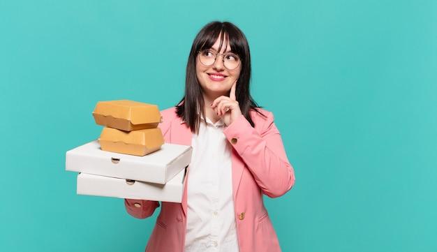 Jonge zakenvrouw die vrolijk lacht en dagdroomt of twijfelt, opzij kijkend