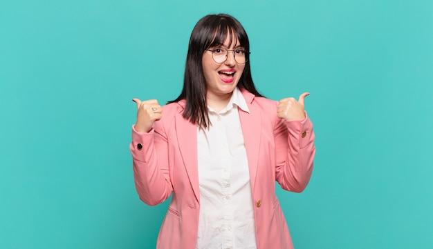 Jonge zakenvrouw die vrolijk lacht en er gelukkig uitziet, zich zorgeloos en positief voelt met beide duimen omhoog