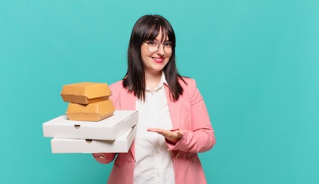 Jonge zakenvrouw die vrolijk lacht, zich gelukkig voelt en een concept in kopieerruimte toont met handpalm