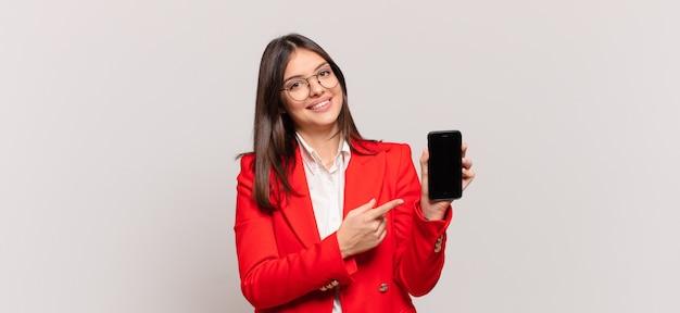 Jonge zakenvrouw die vrolijk lacht, zich gelukkig voelt en naar de zijkant en naar boven wijst, een object in de kopieerruimte laat zien
