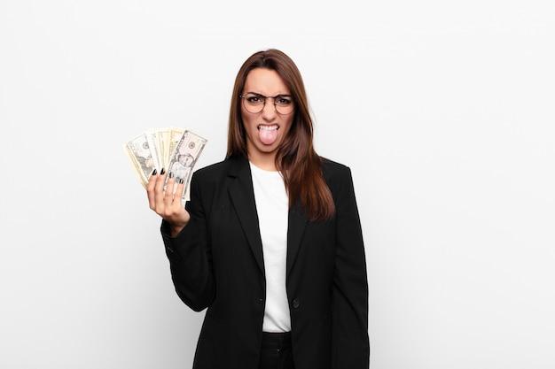Jonge zakenvrouw die walgt en geïrriteerd voelt, tong uitsteekt, een hekel heeft aan iets smerigs en vies met dollarbankbiljetten