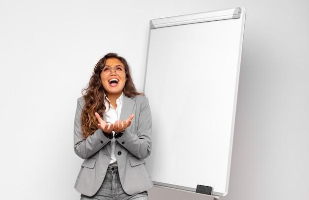 Jonge zakenvrouw die wanhopig en gefrustreerd, gestrest, ongelukkig en geïrriteerd kijkt, schreeuwt en schreeuwt