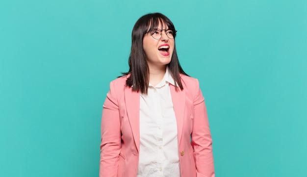 Jonge zakenvrouw die woedend schreeuwt, agressief schreeuwt, er gestrest en boos uitziet