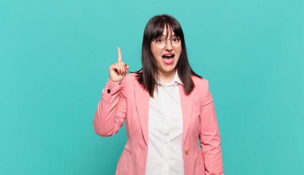Jonge zakenvrouw die zich een gelukkig en opgewonden genie voelt na het realiseren van een idee, vrolijk vinger opstekend, eureka!
