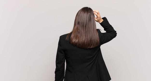 Jonge zakenvrouw die zich geen idee en verward voelt, een oplossing denkt, met de hand op de heup en andere op het hoofd, achteraanzicht