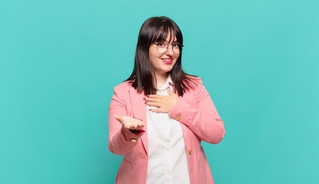 Jonge zakenvrouw die zich gelukkig en verliefd voelt, glimlachend met één hand naast het hart en de andere vooraan gestrekt